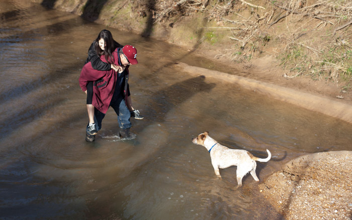 Dad carries Ana across the creek